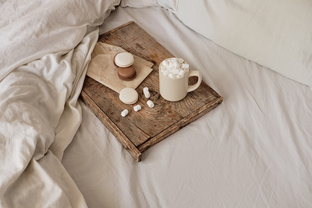 Coffee with marshmallows and macaroons on a wooden tray, in bed. aesthetically beautiful frame. desserts in bed. hot chocolate with marshmallows. cozy and warm day in bed