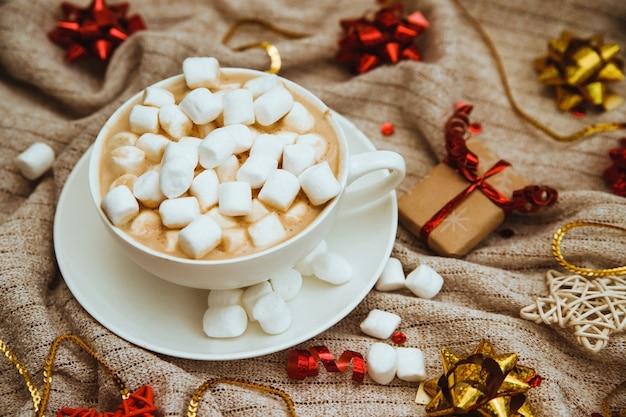 Кофе с зефиром на фоне трикотажной ткани с подарками и праздничными бантами