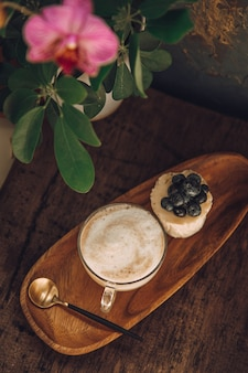 Coffee with milk and a cake with berries on a wooden table in a cafe. orchid decorates a table in a cafe