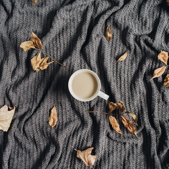 Coffee with milk and dry fall autumn leaves on warm grey plaid