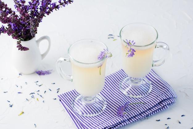 グラスにミルク、泡、ラベンダー、白いテーブルの上の水差しに花の花束とコーヒー。コピースペース