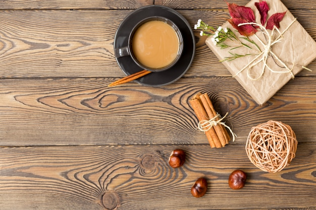 Coffee with milk, gift, autumn leaves, cinnamon sticks and chestnuts on wooden background.