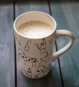 Coffee with milk in a high white mug with a drawing of animals closeup on a turquoise wooden tray