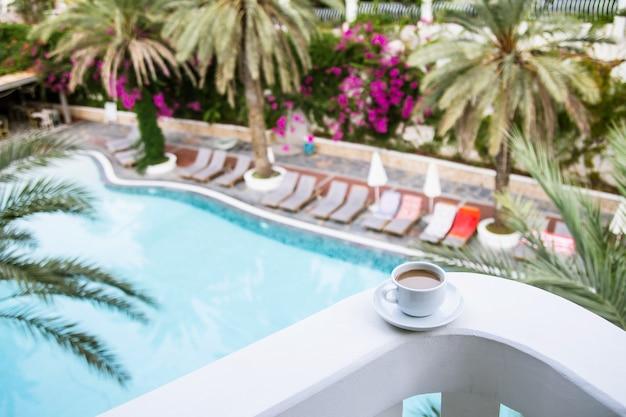 호텔 발코니에 흰색 컵에 우유와 커피.