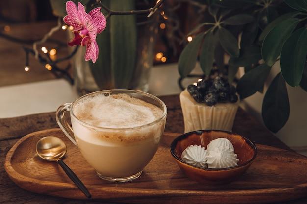 カフェでの朝食用のコーヒー、ミルク、メレンゲ、ベリーのケーキ。木製のテーブルと蘭