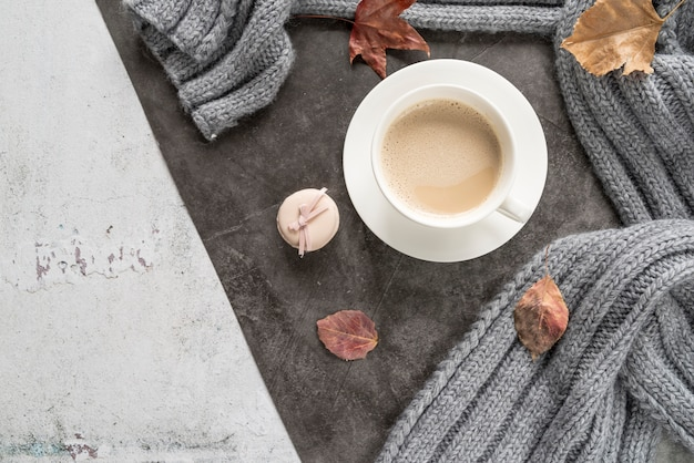 Coffee with milk and warm sweater on shabby surface