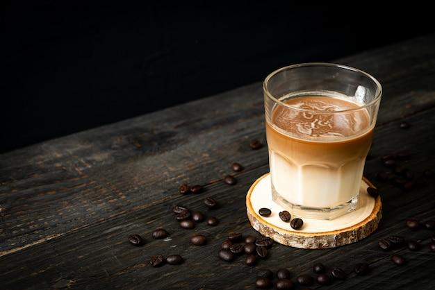 Кофе с молоком с кофейными зернами на деревянной поверхности