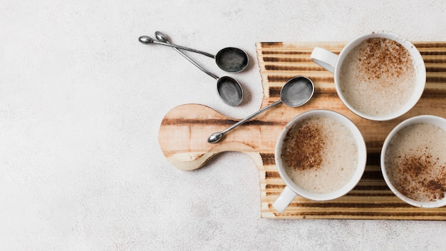 Coffee with milk on wooden board with spoons