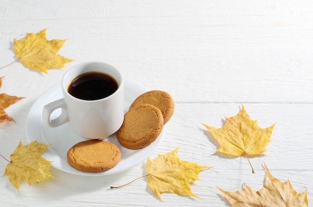 Кофе с овсяным печеньем и желтыми осенними листьями