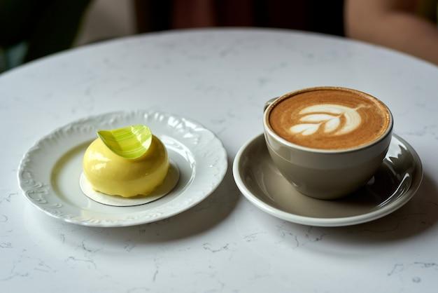 ペストリーとコーヒー。トレンディなカフェスタイルのコーヒーとムースのケーキ。カプチーノのカップとケーキ。モダンなカフェで完璧な朝食。