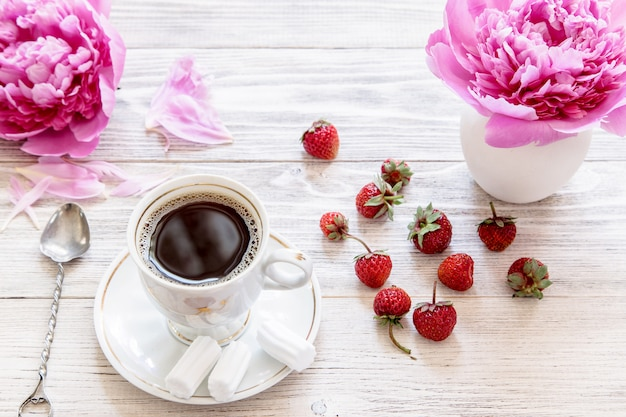 Coffee with pink flower and strawberry on wooden table