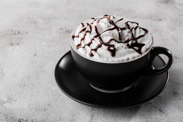 Coffee with whipped cream and chocolate topping. iced coffee in dark cup isolated on bright marble background. overhead view, copy space. advertising for cafe menu. coffee shop menu. horizontal photo.