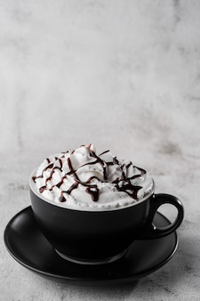 Coffee with whipped cream and chocolate topping. iced coffee in dark cup isolated on bright marble background. overhead view, copy space. advertising for cafe menu. coffee shop menu. vertical photo.