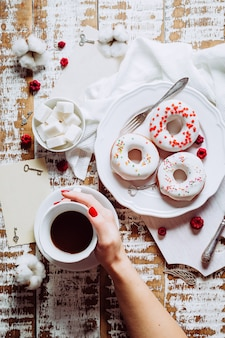 Coffee in a woman's hand and three donuts with white glaze. valentine's day