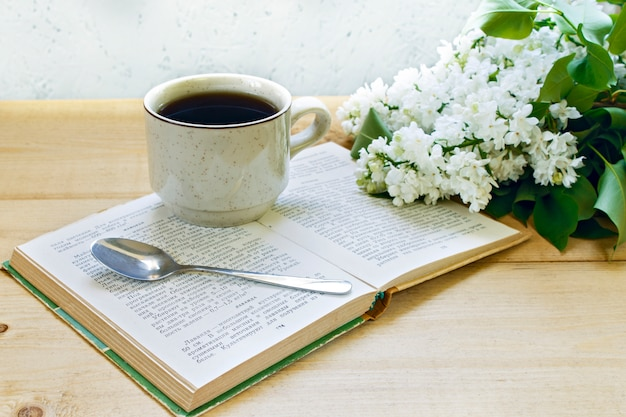 Coffee on a wooden background and flowers. lilac. spring. morning.