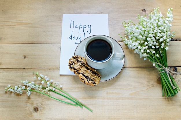 Coffee on a wooden background and flowers. lilies of the valley. spring. morning. march 8. women's day