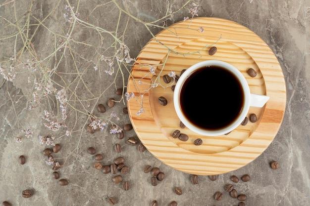 Caffè sul piatto di legno con chicchi di caffè.