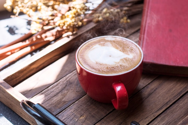 Coffee on wooden tray with warm morning light near the window