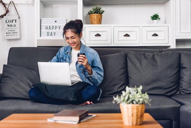 Молодая усмехаясь счастливая красивая азиатская женщина ослабляя используя работу портативного компьютера и видеоконференцию встречая онлайн чат дома. молодая творческая девушка выпивает coffee.work от домашней концепции