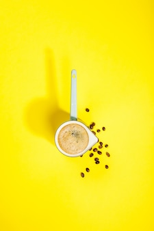 Coffee on yellow table, flat lay, top view