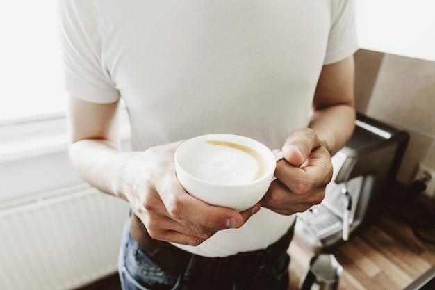 若い男が自宅で自動coffeemachineでコーヒーを調理します。