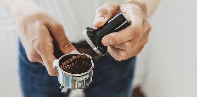 若い男が自宅で自動coffeemachineでコーヒーを調理します。水平。バナー。