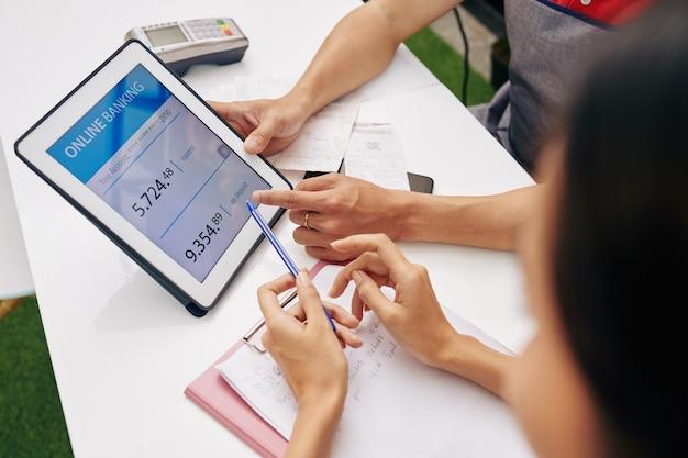 커피 숍 주인은 태블릿 컴퓨터에서 애플리케이션을 통해 은행 계좌를 확인하고 회의에서 수입과 지출에 대해 논의합니다.