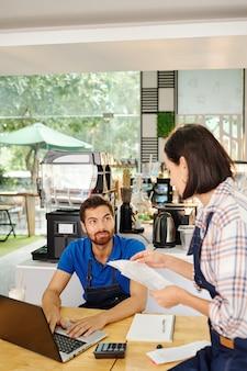 Владельцы кофейни сидят за столом и обсуждают финансы, доходы и