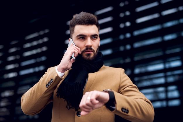 Cofindent человек разговаривает по телефону, проверка времени на наручных часах
