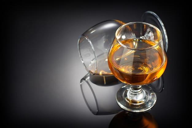Коньяк и стакан на черном фоне