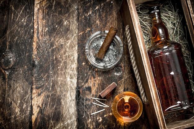 コニャックの背景。ガラスと葉巻が入った箱に入ったコニャックのボトル。木製の背景に。