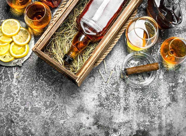 Cognac background. a bottle of cognac with lemon wedges and a cigar. on a rustic background.