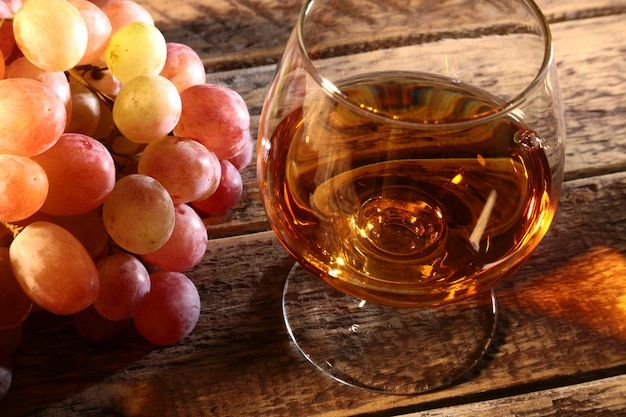 Cognac or brandy in a glass and fresh grapes, still life in rustic style, vintage wooden background, selective focus.