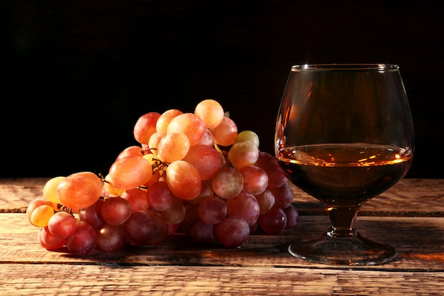 Cognac or brandy in a glass and fresh grapes, still life in rustic style, vintage wooden background,