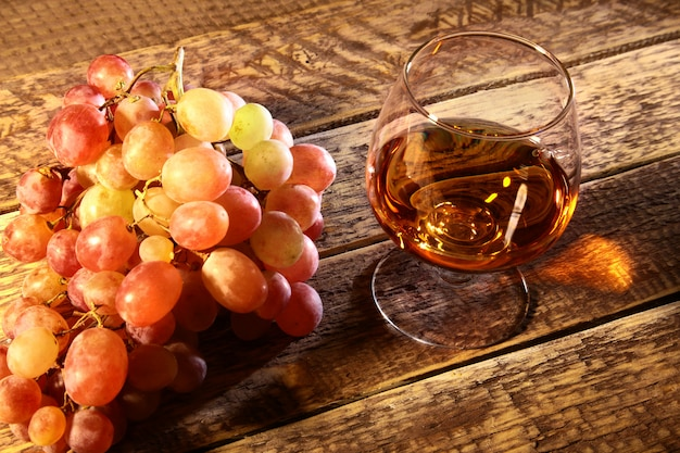 Cognac or brandy in a glass and fresh grapes, still life in rustic style, vintage wooden , selective focus.