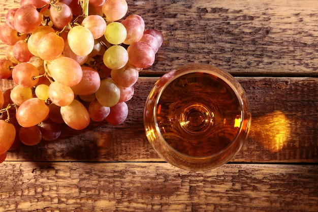 Cognac or brandy in a glass and fresh grapes, still life in rustic style