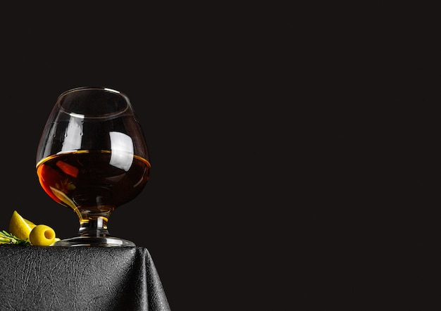 Cognac in a glass on a black background on the table, olives and a slice of lemon
