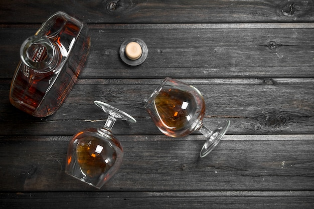 Cognac in a glass bottle and glasses. on black wooden