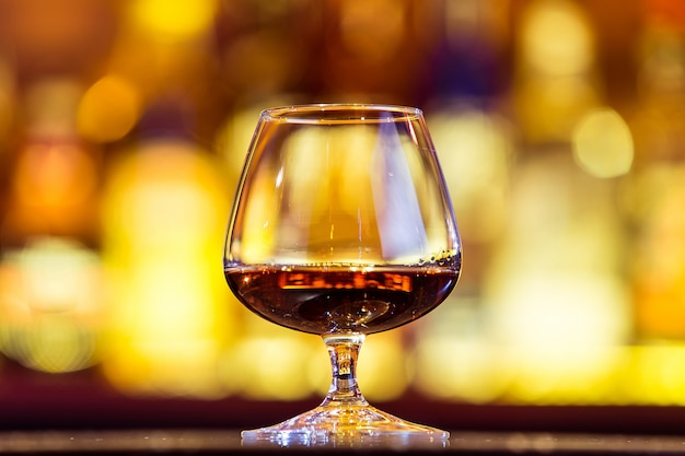Cognac in a glass on bright lights. traditional french drink.