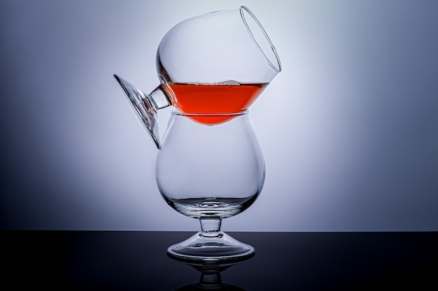 Cognac glasses with a drink on a dark background. dishes for cognac and other drinks