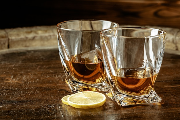 Cognac in glasses with lemon pieces over wooden table