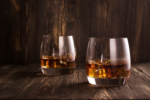 Cognac in glasses over wooden table