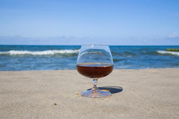 푸른 바다의 해안에 유리에 코냑. 남쪽에서 술과 함께 지내다