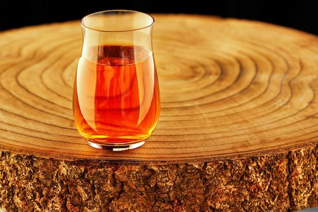 Коньяк в специальном бокале на деревянной подставке