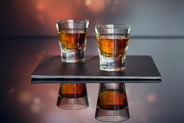 Коньяк или ликер, кофейные зерна и специи на стеклянном столе