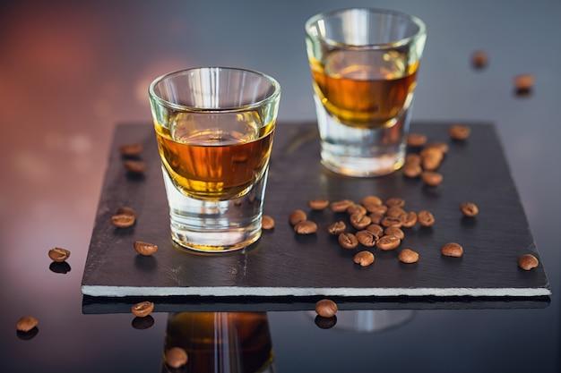 コニャックまたはリキュール、コーヒー豆、ガラステーブルの上のスパイス