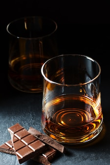Коньяк или ром или бурбон в бокале. кусочки шоколада. дегустация алкоголя