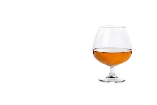 白い背景で隔離のコニャックまたはウイスキーの飲み物