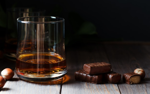 Коньяк или виски или бренди в стакане. кусочки шоколада и фундука.