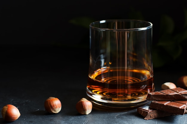 Cognac or rum or bourbon in a glass. pieces of chocolate and hazelnuts.